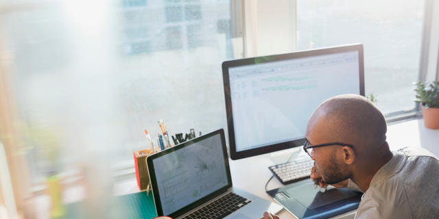 Image shows a man wearing glasses and working at two computer screens.